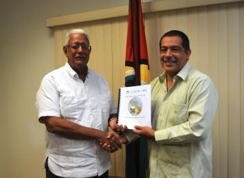 IICA's Country Representative, Mr. Wilmot Garnett, hands over the document to Agri. Minister, Noel Holder