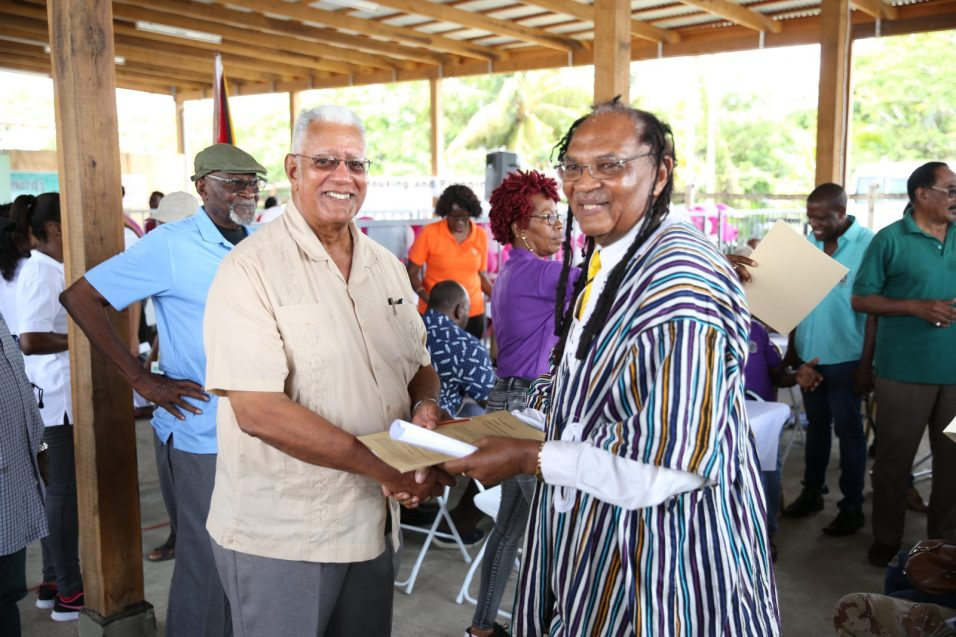 Ras Dalgety receives his lease from Minister of Agriculture, Noel Holder