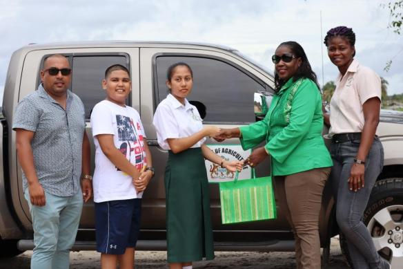 Minister Valerie Adams-Yearwood while making the presentation to Riana Toney in the presence ofher father, brother and another Ministry official