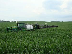 A large sprayer applies nitrogen fertilizer to a field. The equipment is assisted by technology that optimizes the application of fertilizer—using it only where needed on the field. This reduces cost to the grower. Photo credit: Bill Raun