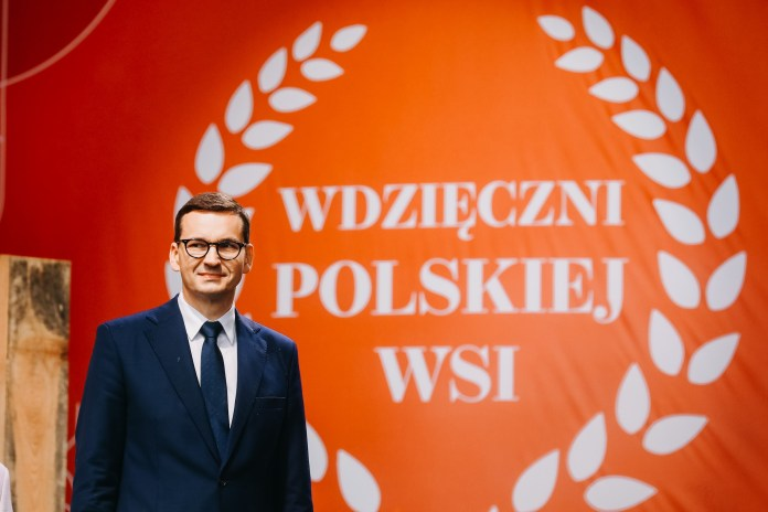 """Premier na tle napisu """"Wdzięczni polskiej wsi"""""""