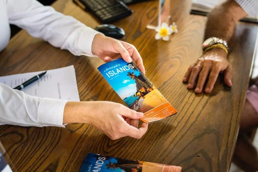 people handling a brochure