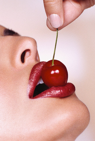 Woman holding cherry to mouth