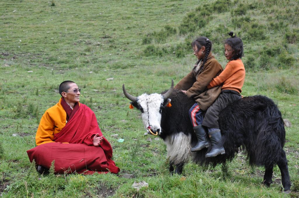 His Holiness Gyalwai Nyugu Rinpoche with two Tibetan girls riding a small animal