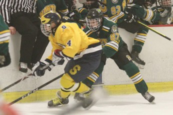 Glenbrook South's Gavin Miller (left) battles for a puck with Glenbrook North's Jonathan Ovnanyan