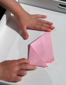 child making simple origami flower