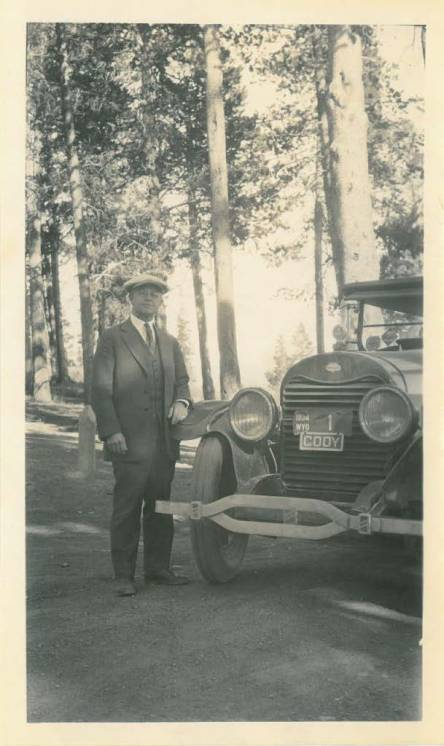 Jacob M. Schwoob standing next to an old car, featuring his Wyoming license plate number 1.
