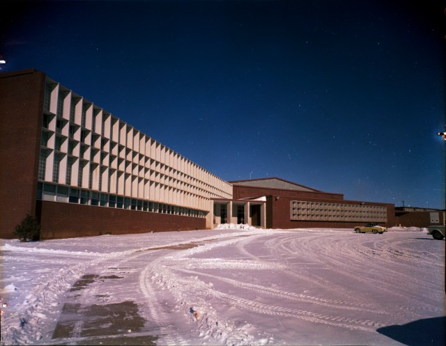 A color photo of the entrance to the former Laramie High School. There is snow on the ground in front of the building.