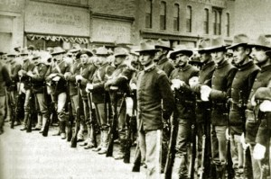 Black and white photograph of men in uniform standing in a line along a street. All are holding rifles.