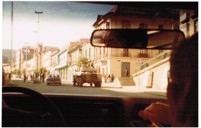 From perspective of sitting in back seat of a car. Two people in front seat; can see one person in rear view mirror. In the street are a car and a military tank. There are several brick buildings on the right side of the street.