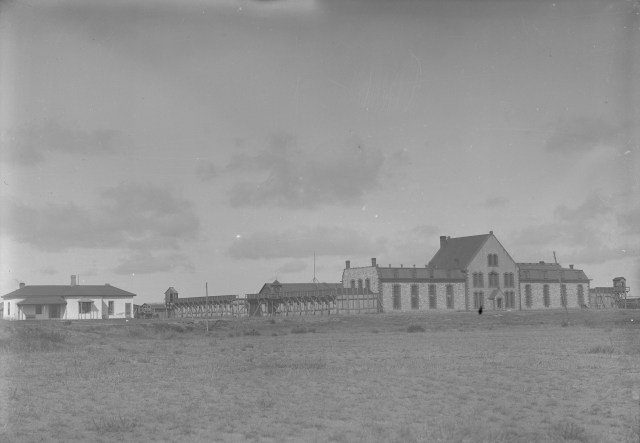 black and white image of two older buildings -- one is a prison
