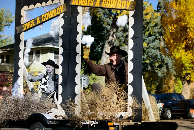 "two people on a parade float that reads ""Once a Cowboy, Always a Cowboy"""