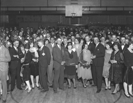 large group of dressed up people standing in gymnasium