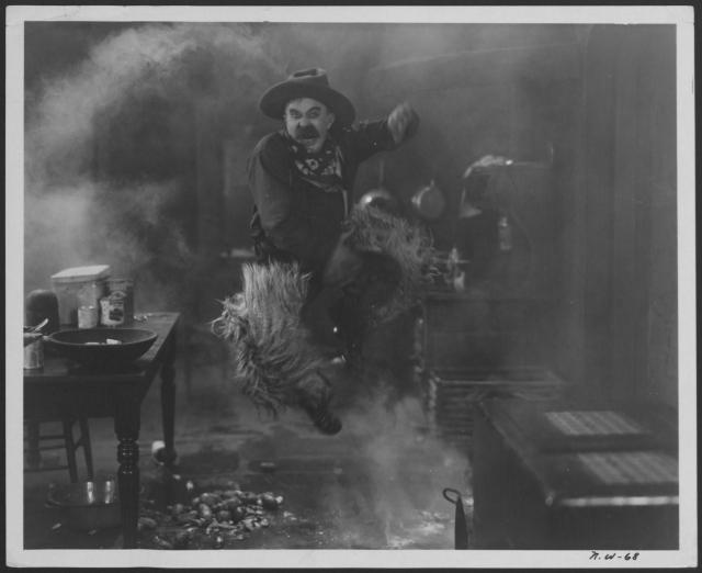 man in cowboy outfit in kitchen jumping