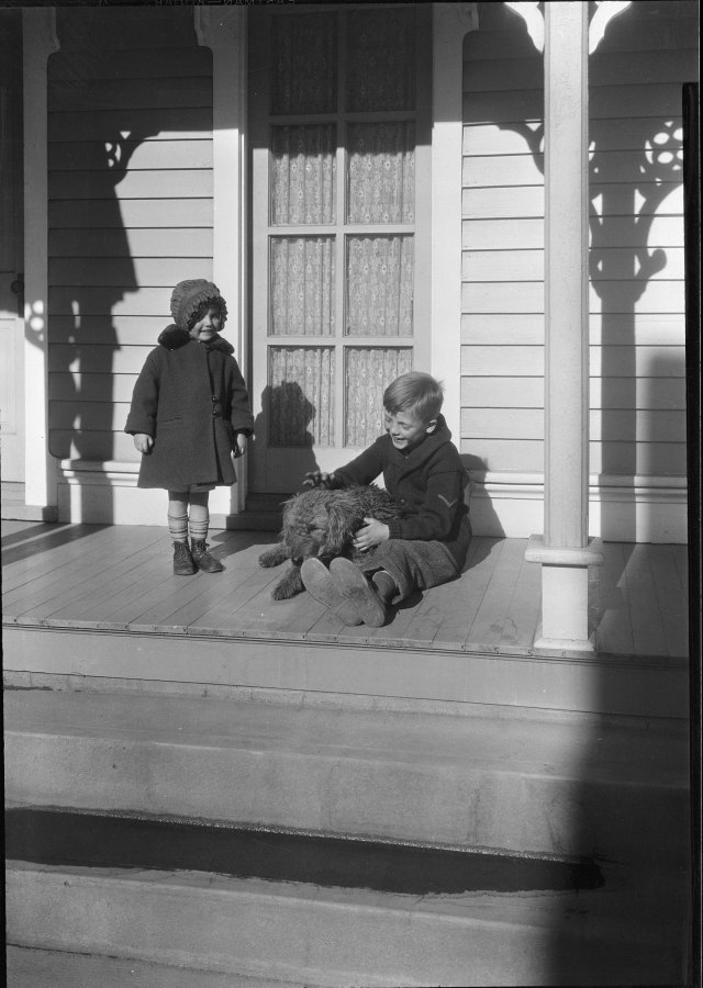 two children and a dog sitting on a porch outside.