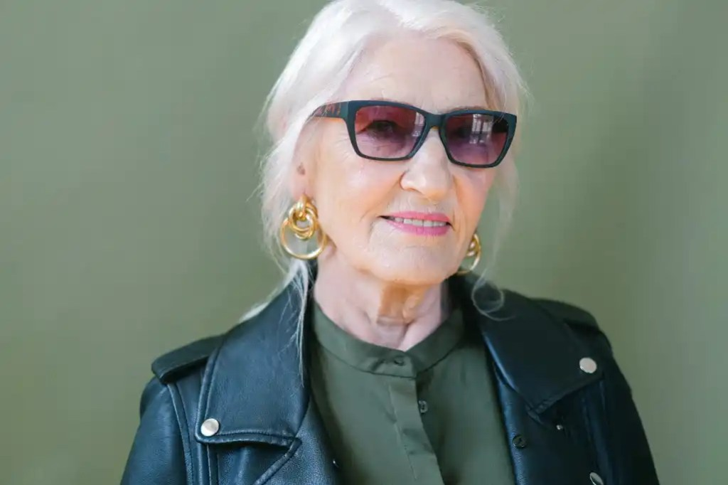 elderly woman in sunglasses and leather jacket in studio
