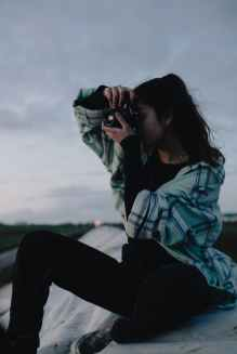 young woman taking photos on roof in countryside