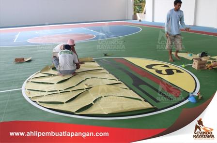 menempelkan kertas mal/pola pada lantai lapangan olahraga untuk di tandai