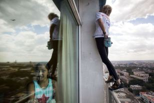 """Alain Robert of France, who is known as """"Spiderman"""", climbs up the Habana Libre hotel as a youth looks out a window in Havana February 4, 2013. Robert, who scales buildings all over the world without safety equipment, successfully climbed the hotel which is 126 metres (413 feet) high. REUTERS/Ramon Espinosa/Pool"""