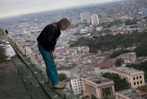 """Alain Robert known as """"Spiderman,"""" looks over the edge from the roof of the Habana Libre hotel in Havana, Cuba, Friday, Feb. 1, 2013. (AP Photo/Ramon Espinosa)"""