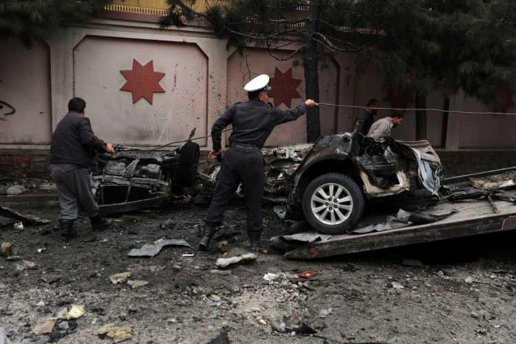Miembros de las fuerzas de seguridad de Afganistán retiran un auto dañado por una explosión, en Kabul, Afganistán, el 20 de febrero de 2021. (AP Foto/Rahmat Gul)