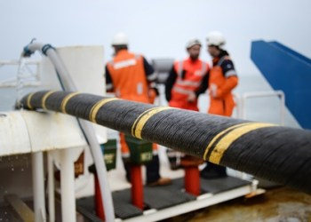 Employees of ERDF (Electricity Network Distribution France) and Louis Dreyfus company install an electric submarine cable and optical fiber between Quiberon and Belle-Ile-en-mer, western France, on March 11, 2015. The underwatered power line of 15km is installed by ERDF to connect the Brittany island of Belle-Ile-en-mer inhabited by 5000 people. AFP PHOTO / JEAN-SEBASTIEN EVRARD / AFP PHOTO / JEAN-SEBASTIEN EVRARD