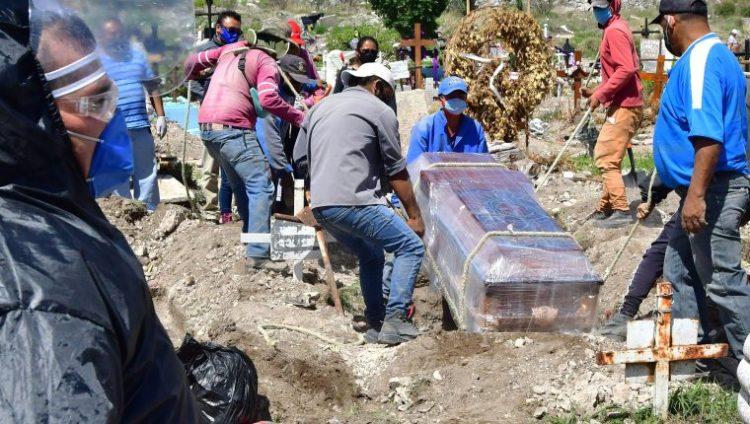 AME791. ECATEPEC (MÉXICO), 04/07/2020.- Fotografía fechada el 2 de julio de 2020 que muestra trabajadores municipales mientras introducen a una fosa un féretro desinfectado en el panteón de San Isidro, en el municipio de Ecatepec (México). La pandemia del coronavirus ha impactado con fuerza a las populosas ciudades del Estado de México, región que colinda con la capital mexicana, donde muchos ciudadanos no creen que exista la enfermedad a pesar de que se duplicaron los fallecidos de la COVID-19 durante la segunda mitad de junio. EFE/Jorge Núñez