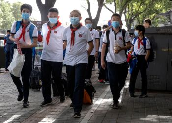 Students wearing masks to curb the spread the new coronavirus leave after the end of a school day in Beijing on Wednesday, June 3, 2020. Students in the Chinese capital have been slowly returning to school as authorities continue to restore normalcy after the shutdown over the coronavirus outbreak. (AP Photo/Ng Han Guan) ///