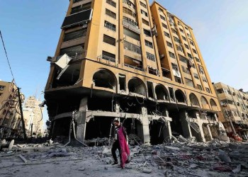 TOPSHOT - A Palestinian man walks amid the rubble early on May 12, 2021 in front of the heavily-damaged Al-Jawhara Tower in Gaza City which was hit by Israeli airstrikes overnight. - Israeli air raids in the Gaza Strip have hit the homes of high-ranking members of the Hamas militant group, the military said Wednesday, with the territory's police headquarters also targeted. (Photo by MAHMUD HAMS / AFP)