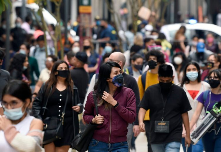 People walk in downtown in Mexico City on December 16, 2020, amid the COVID-19 pandemic. (Photo by ALFREDO ESTRELLA / AE / AFP)