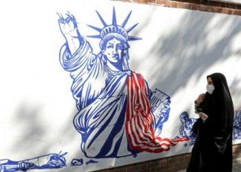 Una mujer pasa frente a un mural con la estatua de la libertad rota, en Teherán, Irán. Foto: AFP