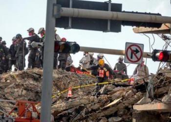 Miembros de un equipo de rescate durante las labores de búsqueda en el edificio Champlain Towers South, derrumbado parcialmente en Surfside, Florida, EEUU.   EFE