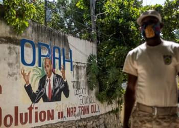 Un policía haitiano ante un mural del presidente Jovenel Moïse en la entrada de la casa donde fue asesinado. Puerto Príncipe, Haití, 11 de julio de 2021. Reuters