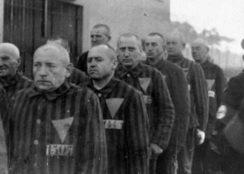Los prisioneros uniformados con insignias triangulares se reúnen bajo la guardia nazi en el campo de concentración de Sachsenhausen. Sachsenhausen, Alemania, 1938. (United States Holocaust Memorial Museum)