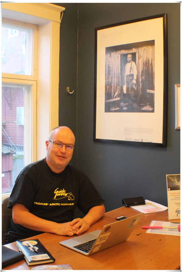 Guide Gunnar sits near a photograph of himself as a young man
