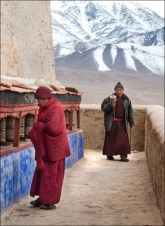 A Buddhist monk and a pilgram making their ascent to the monastery.
