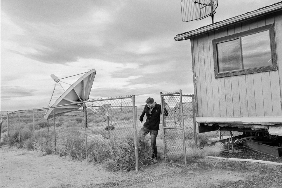 KUYI station manager Richard Davis clears tumbleweed from the station's satellite receiver.