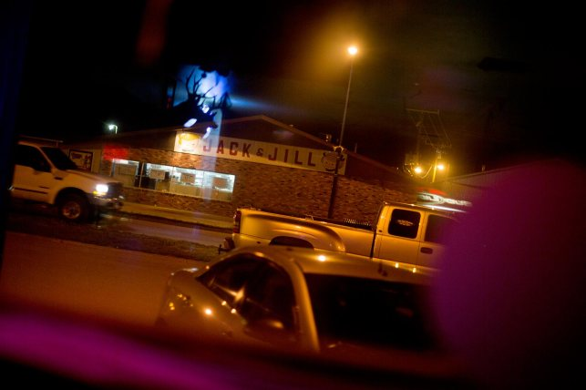 In this June 14, 2015 photo, Kennbeck's Jack & Jill, a local grocery store, is seen through the window of the Player's Pub bar and pool hall on Main Street. © Kristina Barker