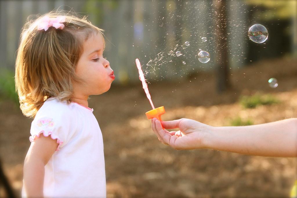 Photogrpahie d'une enfant soufflant des bulles pour le projet de la fête du jeu