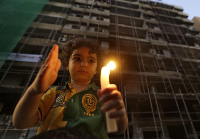 طفل لبناني يحمل شمعة أمام مبنى مدمرّ. Photo Credit: AP