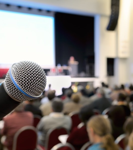 Microphone at conference. Dynamic microphone against the background of convention center. Real photo.
