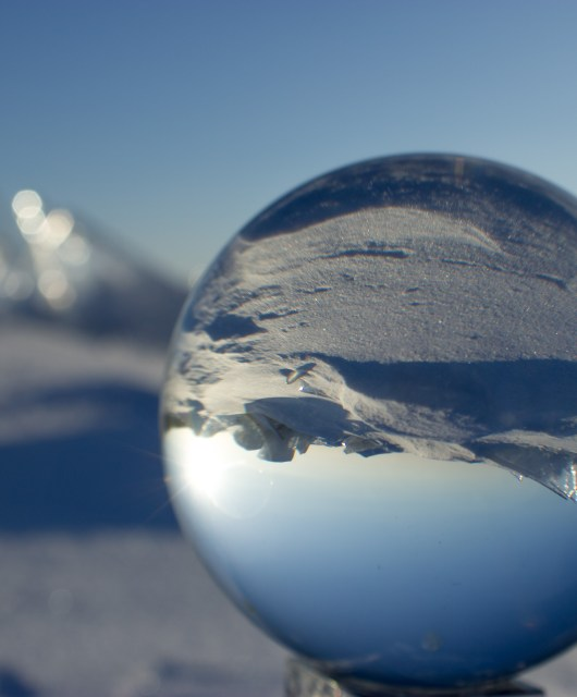 A photograph of a crystal ball in an arctic landscape