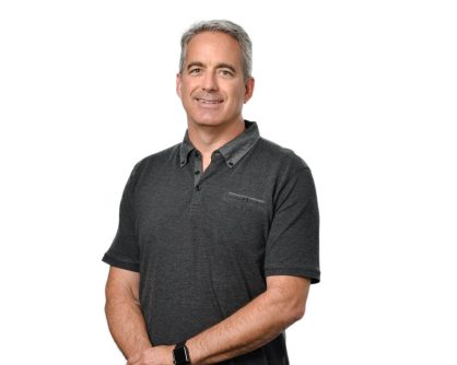 A photograph of Ian Collins, CEO of CrowdCare. CrowdCare provide AI-assisted customer care solutions, such as Wysdom. Ian is wearing a grey polo shirt.