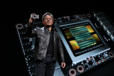 A photograph of Nvidia CEO Jensen Huang holding the new Volta GPU