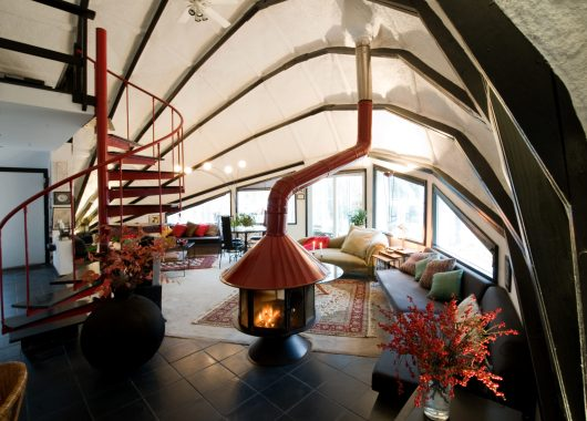 A photograph of a 'quirky' Airbnb property. It has a strange curved ceiling, spiral staircase, log burner, and other interior design quirks for your comfort and convenience.
