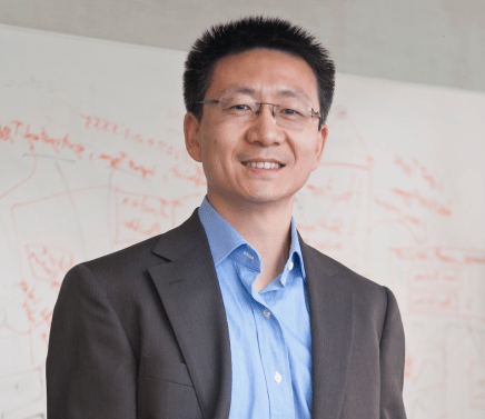 A photograph of Dr. Hui Cheng, Head of R&D Robotics at JD.com, one of the largest Chinese retail giants. He is smiling and standing in front of a whiteboard covered in science.