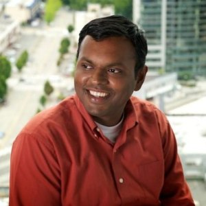 A headshot of Swami Sivasubramanian, VP of Amazon AI at Amazon Web Services. He is smiling and wearing a red polo shirt.