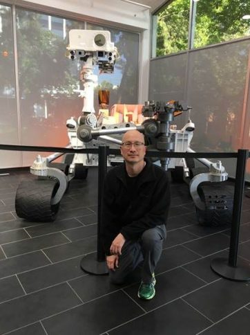 A photo of Steve Chien, Head of AI, JPL, NASA, with Mars Rover