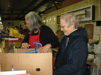 Sr. Carol helps to box items at the front check-out counter.