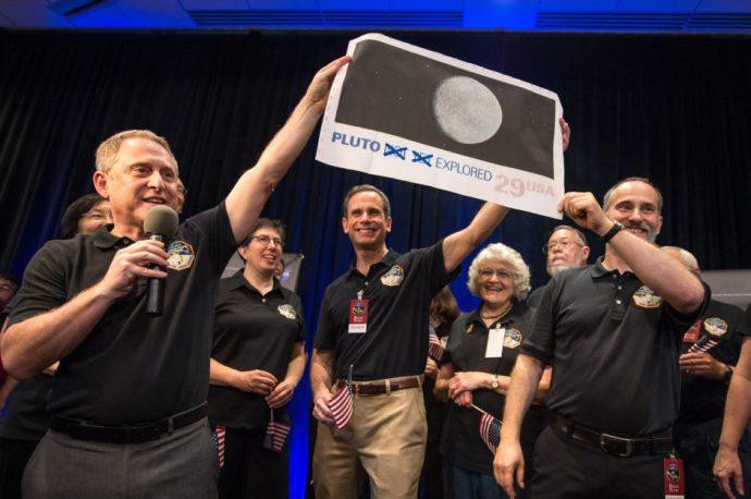Alan Stern, líder del equipo de la sonda espacial New Horizons, sostiene una reproducción de la estampilla con un par de correcciones.